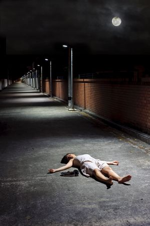 fainted: Female lies dead in the street under a night sky