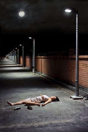 Woman lies vulnerable in the vacant street photo