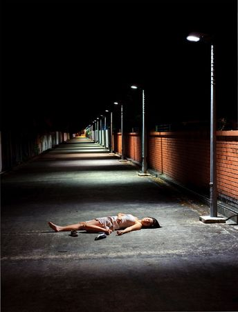 defenseless: Dark and dangerous, girl sleeps in street Stock Photo