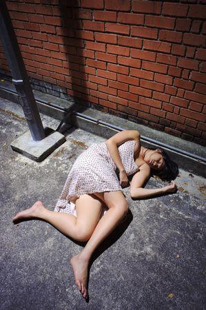 gutter: Asian girl lies in an empty street Stock Photo