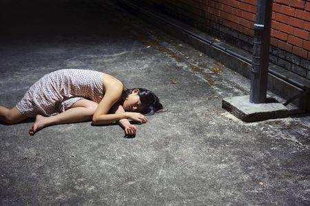 drunk woman: Asian girl lies in an empty street Stock Photo