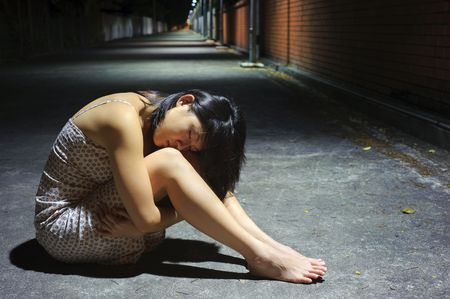 Tired Asian girl rests her head on her knees Stock Photo - 6800706