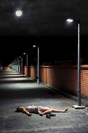 fainted: Asian girl lies in an empty street Stock Photo