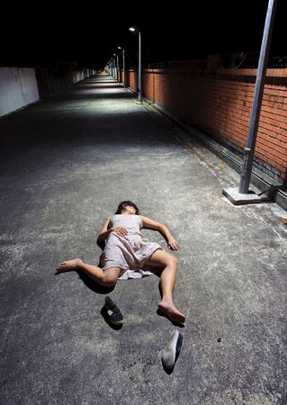 unconscious: Asian girl lies in an empty street Stock Photo
