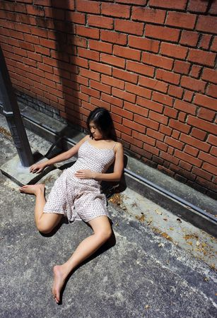 fainted: Asian girl is passed out in the gutter