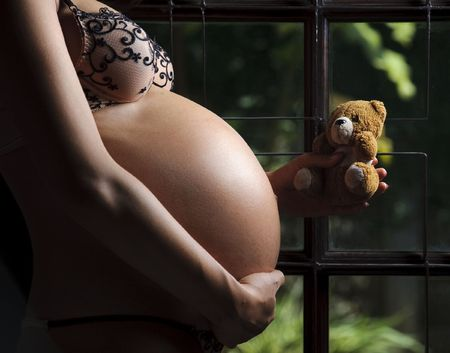 Cute teddy bear and unborn baby become friends photo