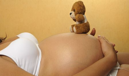 sexy bedroom: Pregnant woman balances a teddy bear on her stomach Stock Photo