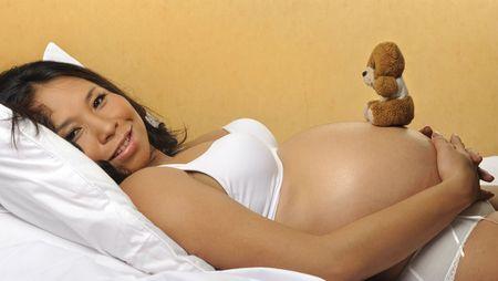 Cute pregnant woman balances a teddy bear on her somach photo