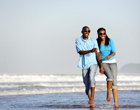Atractiva pareja divirtiéndose juntos en la playa