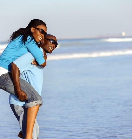 femmes africaines: Couple attrayant, avoir du plaisir ensemble � la plage Banque d'images