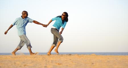 negras africanas: La pareja estadounidense de mano en mano en la playa