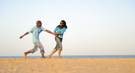 African American couple hand in hand on the beach photo