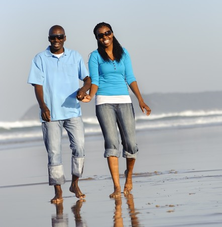 Happy couple walking on the beach in summer photo