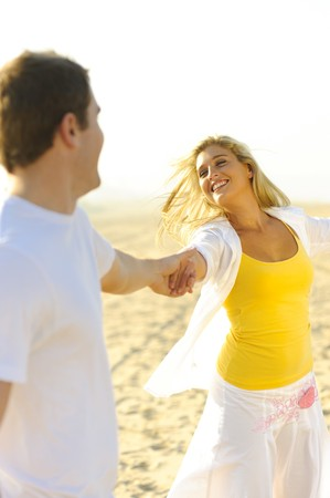boy and girl holding hands: Young couple in love, playing together on the beach