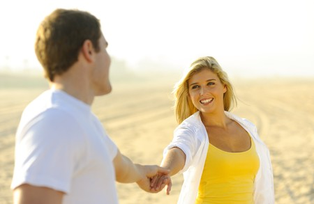 Young couple in love, playing together on the beach photo