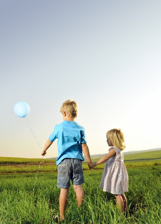 Brother and sister hold hands and hold onto their only balloon Stock Photo - 7378855