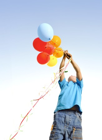 Young boy playing with a bunch of balloons outside Stock Photo - 7378745