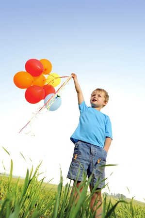 Young boy playing with a bunch of balloons outside Stock Photo - 7378742