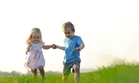 Brother and sister playing together in a field Stock Photo