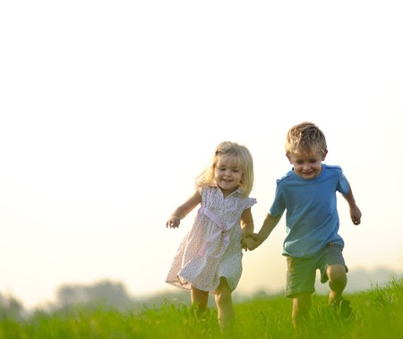 kids holding hands: Brother and sister playing together in a field Stock Photo