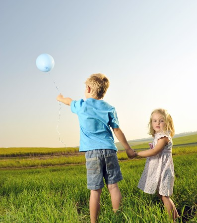 Brother and sister hold hands and hold onto their only balloon photo