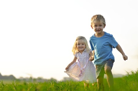 brother: Brother and sister playing together in a field Stock Photo