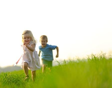 Niña corre a través de un campo, feliz y divirtiéndose.