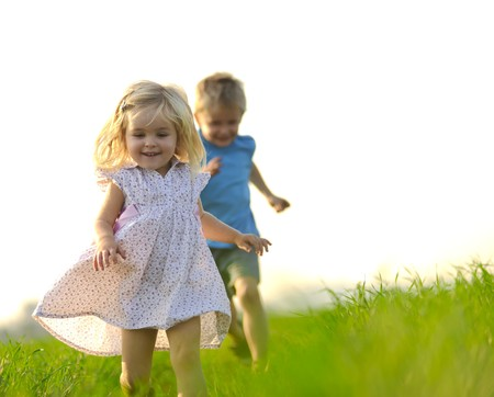 sister: Young girl runs through a field, happy and having fun. Stock Photo