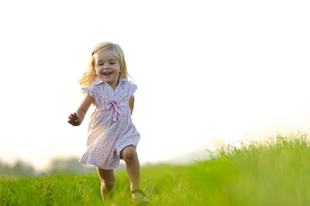 freedom: Young girl runs through a field, happy and having fun. Stock Photo