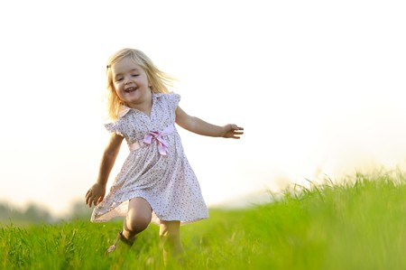 Young girl runs through a field, happy and having fun. Stock Photo - 7378736