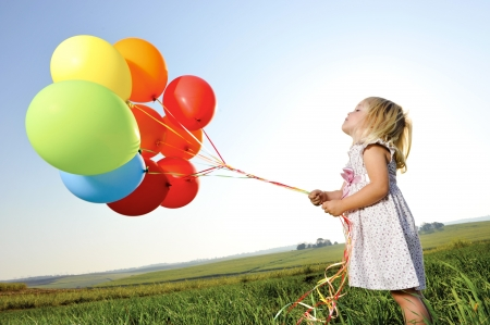Adorable young girl holds tightly to a large bunch of helium filled balloons Фото со стока