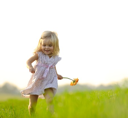 Young girl runs through a field, happy and having fun. photo
