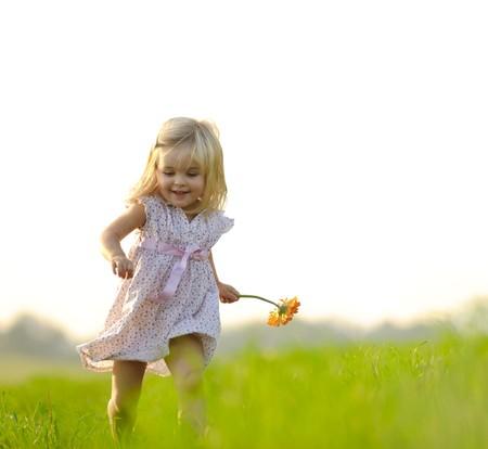 the runs: Young girl runs through a field, happy and having fun. Stock Photo