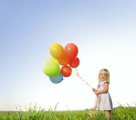 kids dress: Adorable young girl holds tightly to a large bunch of helium filled balloons Stock Photo
