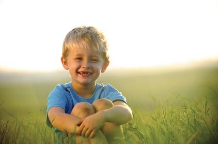 bambini seduti: young boy gode il suo tempo di fuori nel campo  Archivio Fotografico