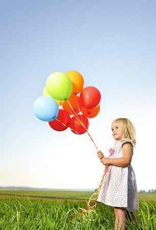 tightly: Adorable young girl holds tightly to a large bunch of helium filled balloons Stock Photo