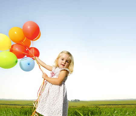 Adorable young girl holds tightly to a large bunch of helium filled balloons photo