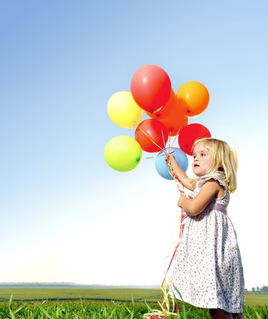 Adorable young girl holds tightly to a large bunch of helium filled balloons Stock Photo