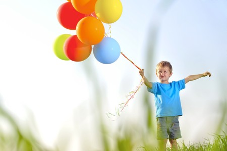 Young boy playing with a bunch of balloons outside, shot through grass in the field photo