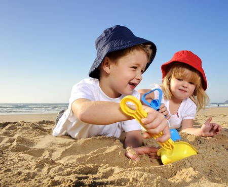 Gorgeous brother and sister ages 4 and 2 have fun digging in the sand at the beach photo