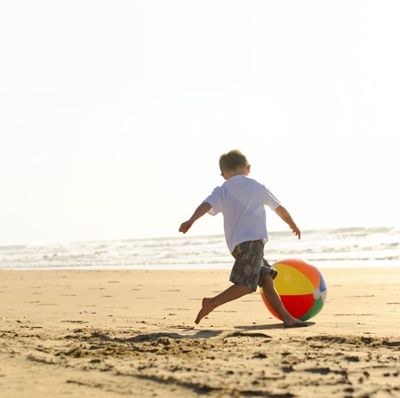 play boy: Young boy at the beach plays with a big beachball