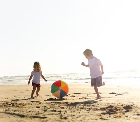 beach ball girl: Hermano hermoso y hermana jugar con una pelota de playa al aire libre  Foto de archivo
