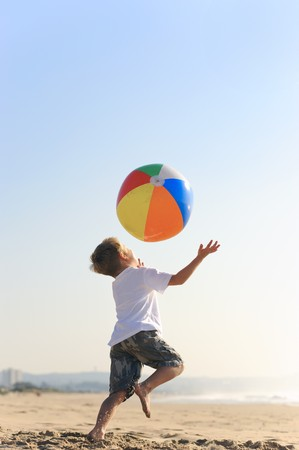 Happy kid throws his beachball in the air and tries to catch it photo