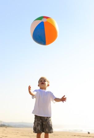 atrapar: Ni�o feliz lanza su beachball en el aire e intenta cogerlo