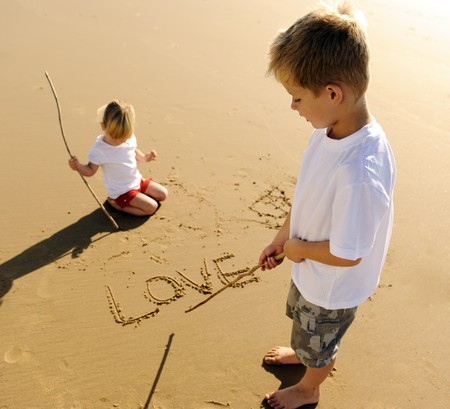Lovely young brother and sister write words in the sand together Stock Photo - 7785541