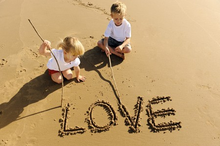 little boy and girl: Lovely young brother and sister write words in the sand together Stock Photo