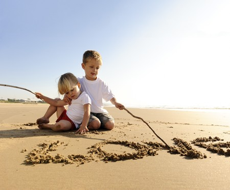 Lovely young brother and sister write words in the sand together Stock Photo - 7785522