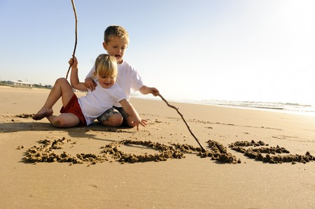 Lovely young brother and sister write words in the sand together Stock Photo - 7776698