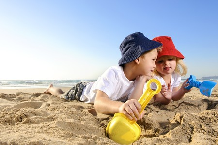 beach hat: Gorgeous brother and sister ages 4 and 2 have fun digging in the sand at the beach