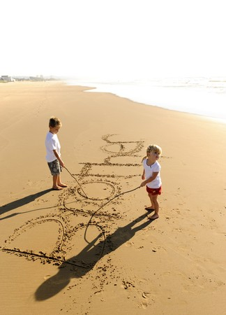 Lovely young brother and sister write words in the sand together Stock Photo - 7785562